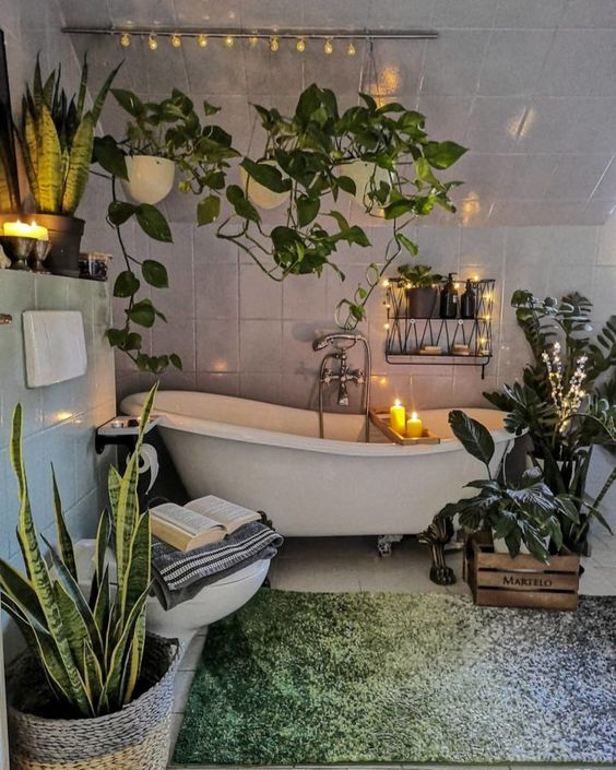 an urban jungle bathroom with climbing plants, potted statement ones, a clawfoot tub and a green rug