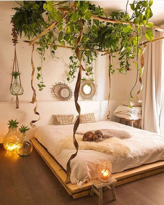 climbing plants covering the canopy of the bed make the bedroom look boho and remind an oasis