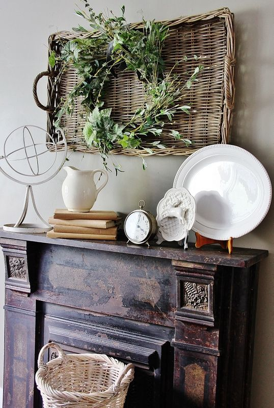 farmhouse mantel decor with a basket tray, a lush textural greenery wreath, some vintage plates and vintage books