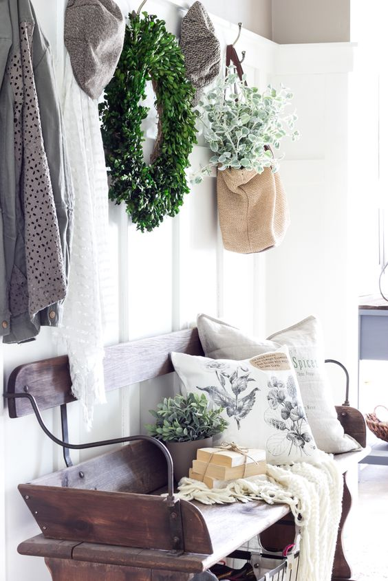 farmhouse spring entryway decor with a greenery wreath, greenery in a burlap bag, greenery in a pot and some botanical pillows