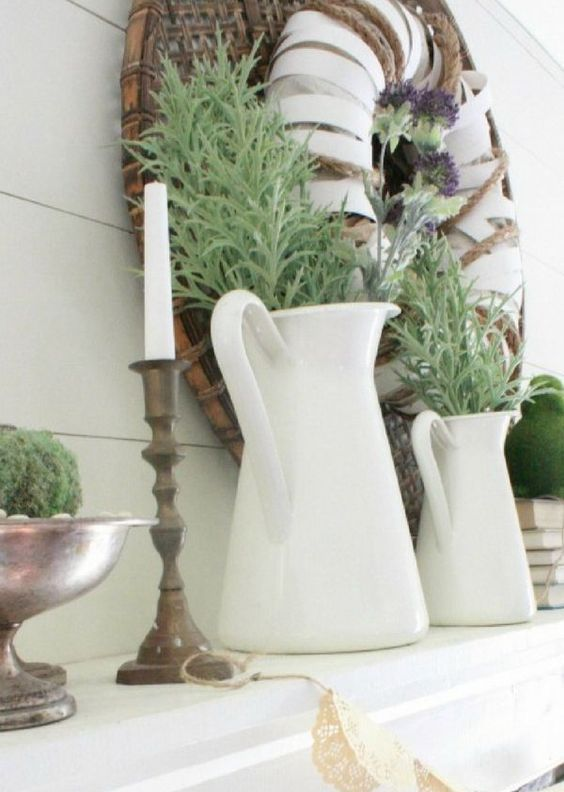 greenery in jugs, candles in wooden candleholders, a wrapped wreath with rope and purple blooms