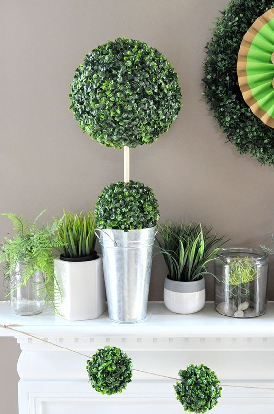potted grass, ferns, greenery topiaries and some greenery ball garlands for a spring-inspired mantel