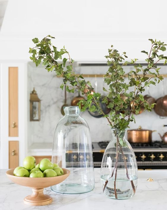 spring decor with green apples in a bowl and some simple greenery in a vase is a modern and easy idea