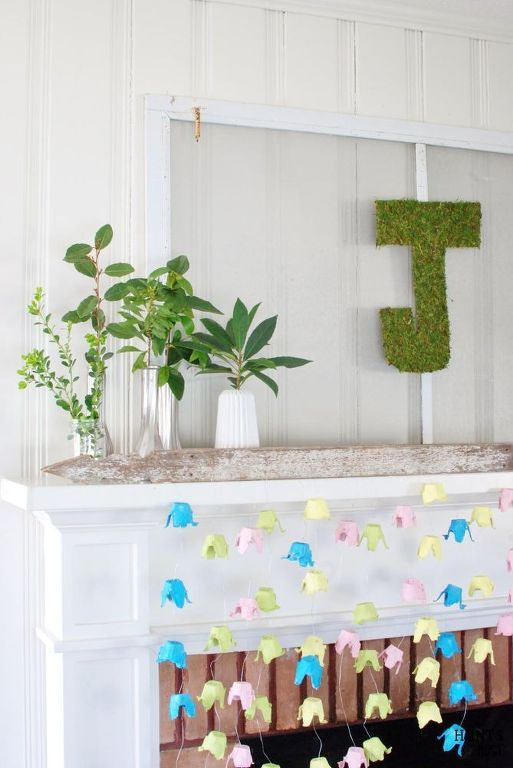 spring mantel and fireplace decor wiht a moss monogram, greenery in mismatching vases and colorful paper blooms