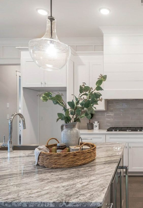 white shaker style cabinets, a grey tile backsplash, grey granite countertops, a glass pendant lamp and some stainless steel appliances
