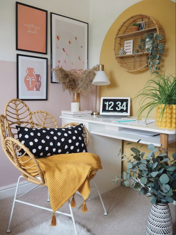 a bright boho working space with a sleek white desk, a rattan chair, a yellow accent and a bold gallery wall in black frames