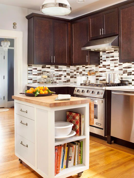 a dark stained kitchen island with a geometric tile backsplash and a small white kitchen island with a butcherblock countertop and storage