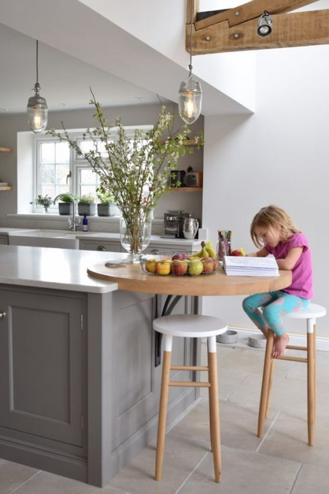 02 a floating round breakfast bar attached to the kitchen island and tall wooden stools are a great and cozy space