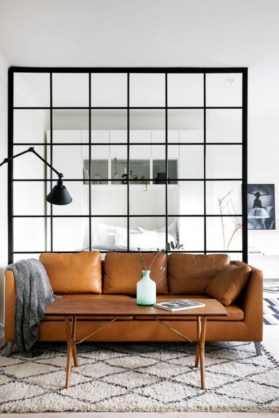 a monochromatic Scandinavian space with a tan leather sofa, a table on trestle legs, a glass space divider and a black lamp