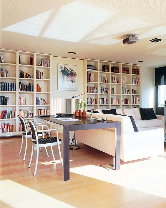 a neutral welcoming living room with built in bookshelves, a creamy sofa with black pillows and a large desk by its isde