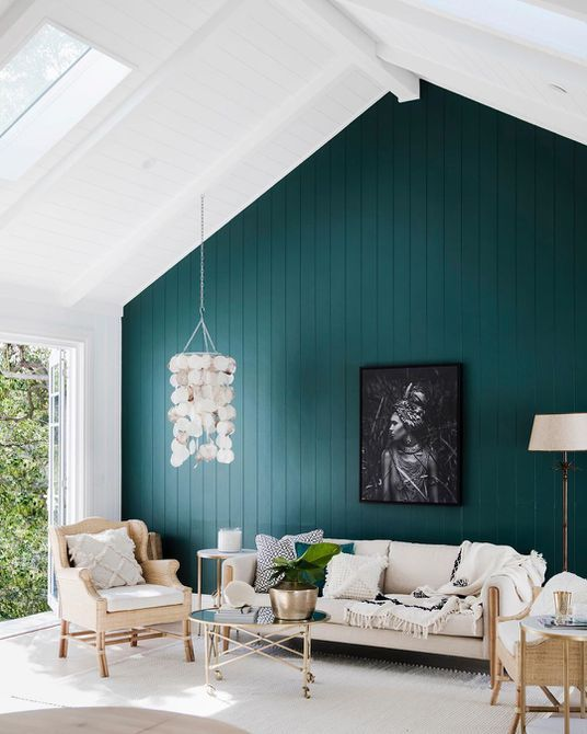 03 a catchy living room with a slanted ceiling, a teal accent wall, a glazed wall, a neutral sofa and chairs, a mother of pearl chandelier