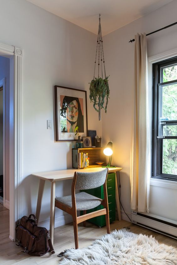 a cool mid-century modern nook with a small desk, a green storage unit, a grey chair, a potted plant, a floor lamp