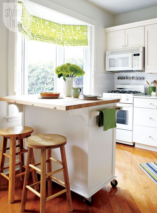 a modern white kitchen with a mobile kitchen with a butcherblock countertop and wooden stools plus green accents here and there