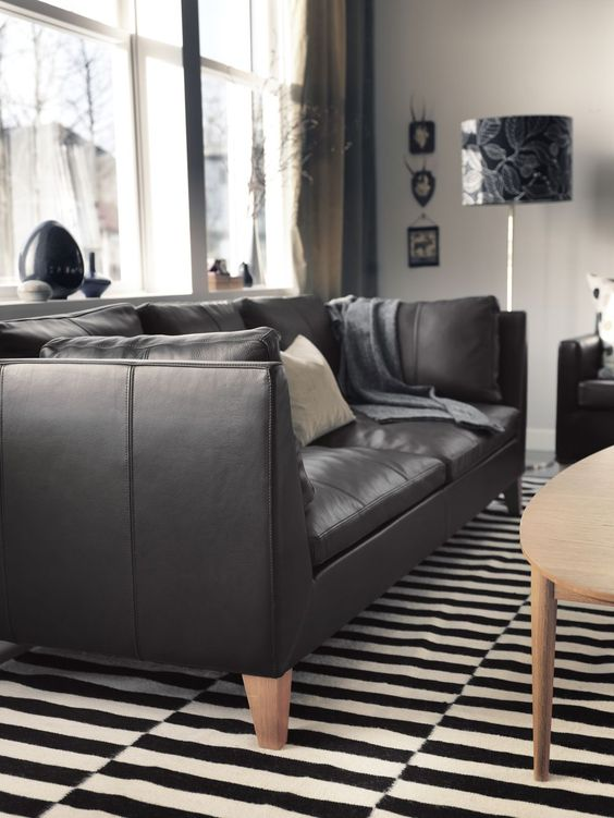 a monochromatic living room with a black leather Stockholm, a wooden table, a floor lamp and vases