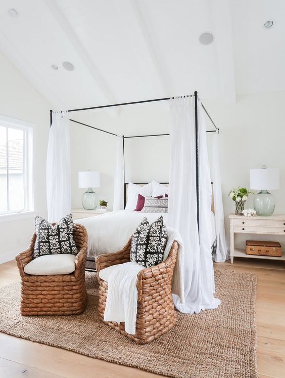 a neutral farmhouse bedroom with a black metal canopy bed with white curtains, neutral nightstands, rattan chairs and neutral bedding
