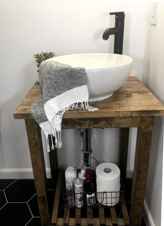 a rustic IKEA Bekvam cart turned into a bathroom vanity, with a bowl sink and a black faucet is a stylish solution