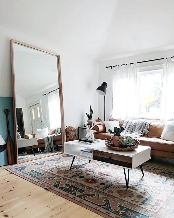 04 a boho living room with a leather sofa, a low coffee table, an oversized mirror in a simple wooden frame is very welcoming