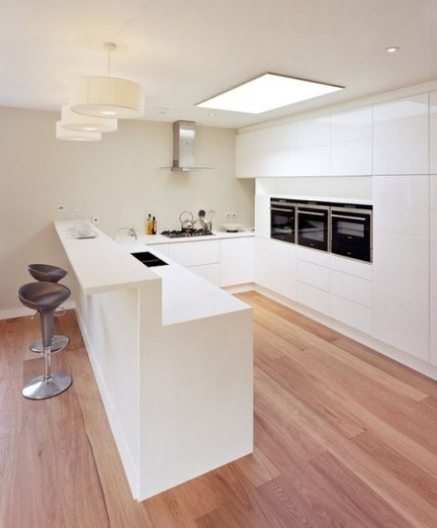 a minimalist white kitchen island with a raised breakfast bar counter and stools for meals and drinks is amazing