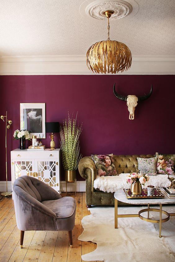 a sophisticated living room with a deep colored accent wall, a chic tufted sofa, a lilac chair, a gold chandelier and refined gold touches