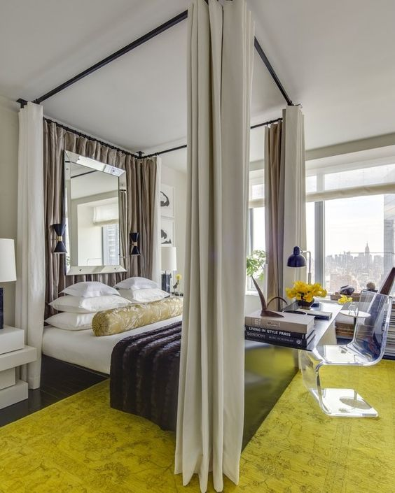a stylish bedroom with a canopy bed with curtains, a mirror, a neon green carpet and an acrylic chair at the desk