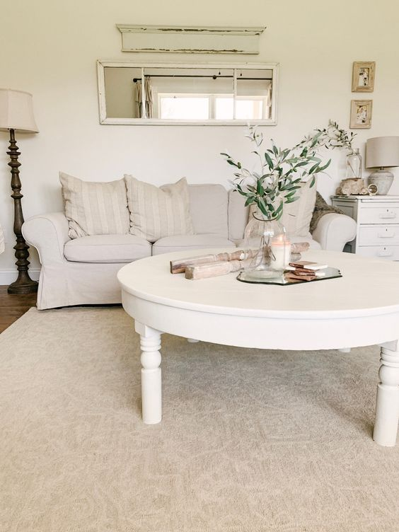 a white shabby chic living room with a creamy Ektorp sofa, a low round table, a nightstand, floor and table lamps