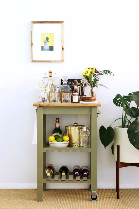 an elegant home bar painted green, with a light stained butcherblock countertop and holders for towels is a lovely idea