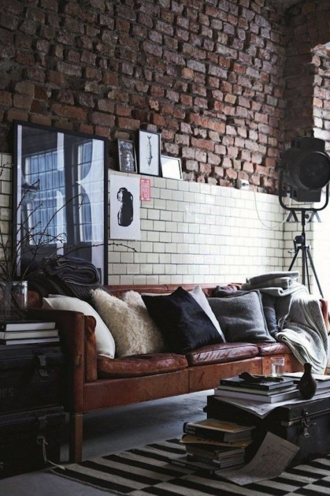 an industrial living room with a brown leather Stockholm sofa that echoes with en exposed brick wall and black and white details around