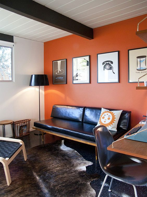 a catchy modern space with an orange accent wall, a black leather sofa, a desk and a chair plus a woven chair