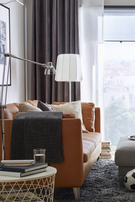 a chic living room with an orange leather Stockholm sofa, mauve curtains, a grey rug, a grey ottoman and a stylish round table