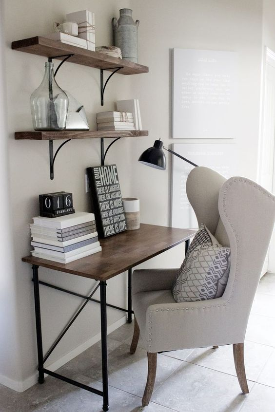 a farmhouse workspace with a stained desk, shelves for storage, a neutral upholstered chair, a floor lamp and stacked books