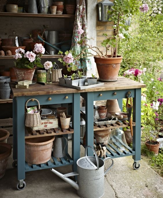 a gardening table made of two IKEA Bekvam carts, with slate blue paint and butcherblock countertops, with hooks and holders