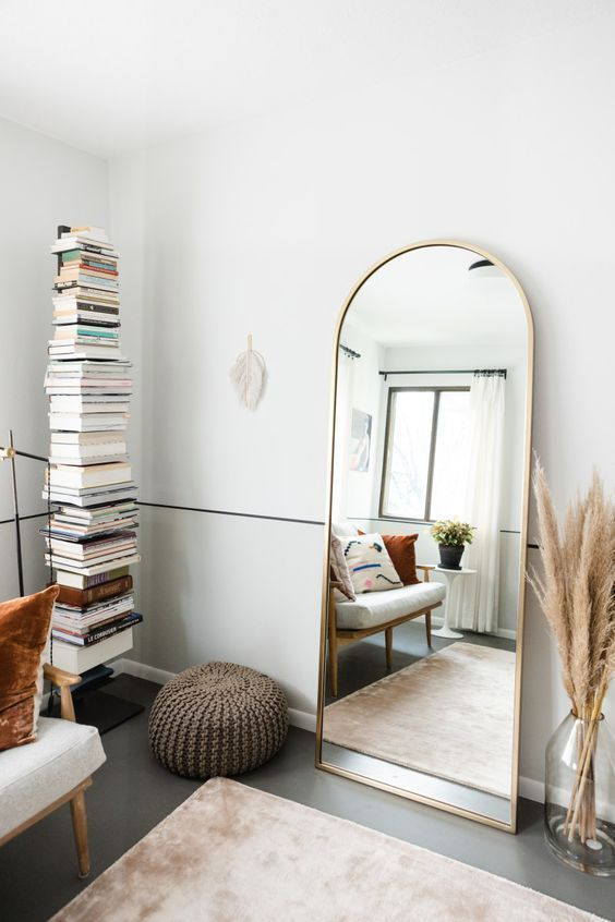 a lovely boho living room with a stack of books, a loveseat, an arched mirror and pampas grass in a bottle