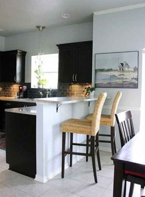 05 a raised up breakfast bar counter as a part of the kitchen island, rattan stools for comfortable sitting