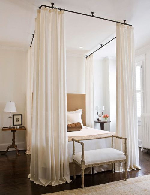 a refined neutral bedroom with a canopy with curtains over the tan bed, mismatching nightstands and neutral bedding