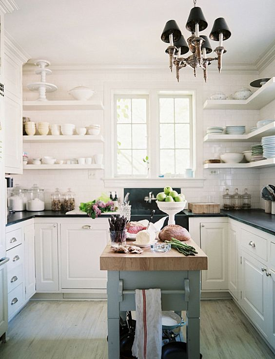 a stylish vintage-inspired kitchen in white, with black coutnertops, a light blue kitchen with with a butcherblock countertop for a color accent