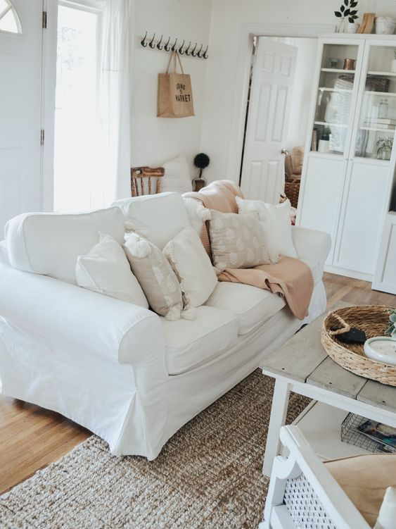 a white farmhouse living room with an Ektorp sofa, white glass cabinets, a low wooden table and chairs is welcoming
