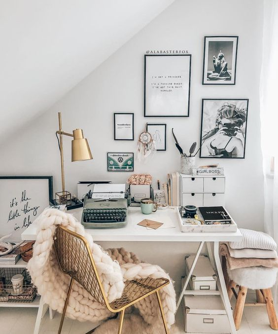 06 a glam workspace with a small white desk, boxes stacked, a gold chair with a blanket, a matching lamp and a black and white gallery wall