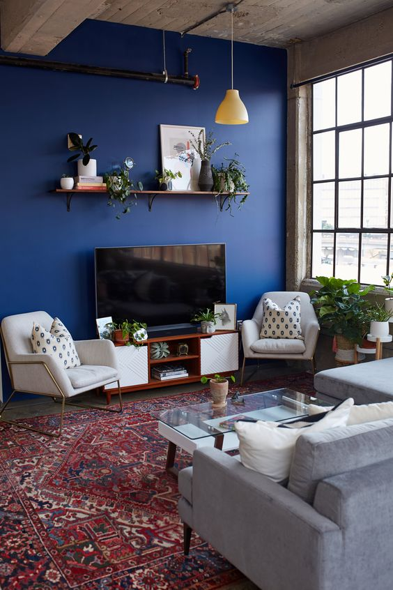 a mid-century modern living room with an electric blue accent wall, neutral furniture, a boho printed rug and potted plants