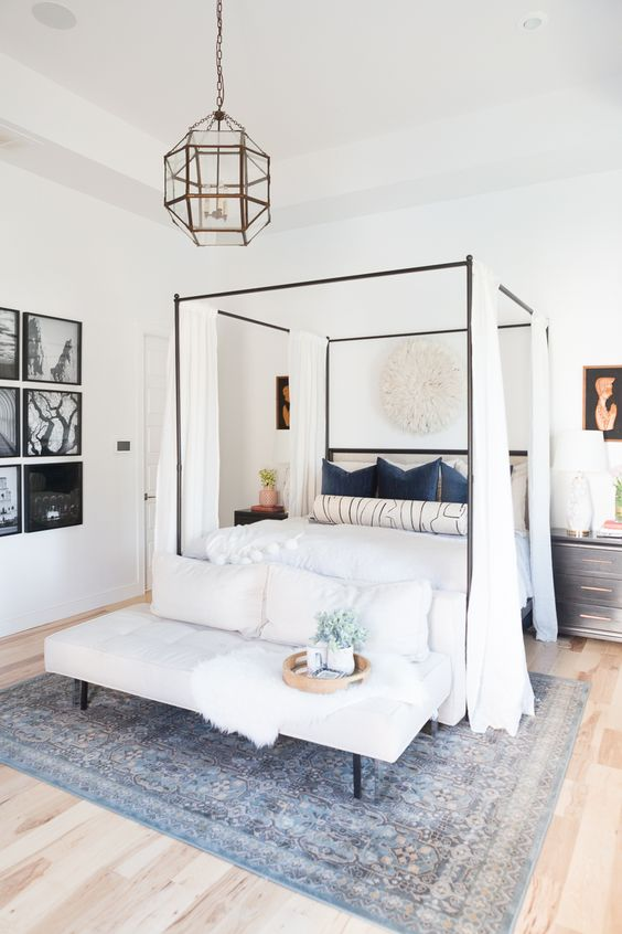 a neutral farmhouse bedroom with a canopy bed styled with curtains, a bench with pillows, a faceted lamp and a gallery wall