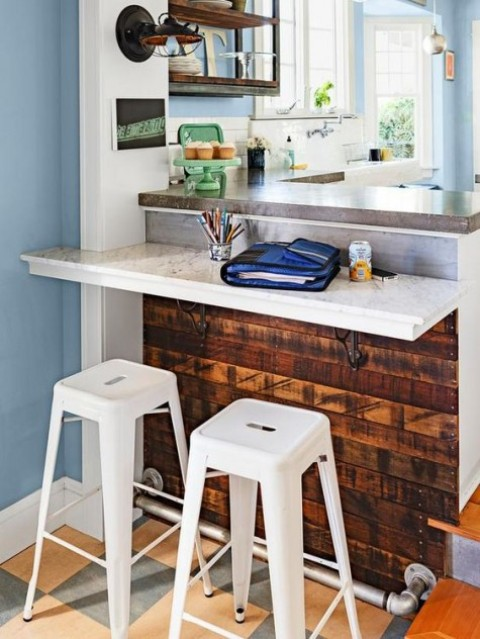 a small breakfast bar attached to the kitchen island and a couple of metal stools for having meals and drinks here