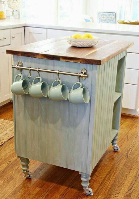 a white farmhouse kitchen with a light blue kitchen island with a butcherblock countertop that adds color here