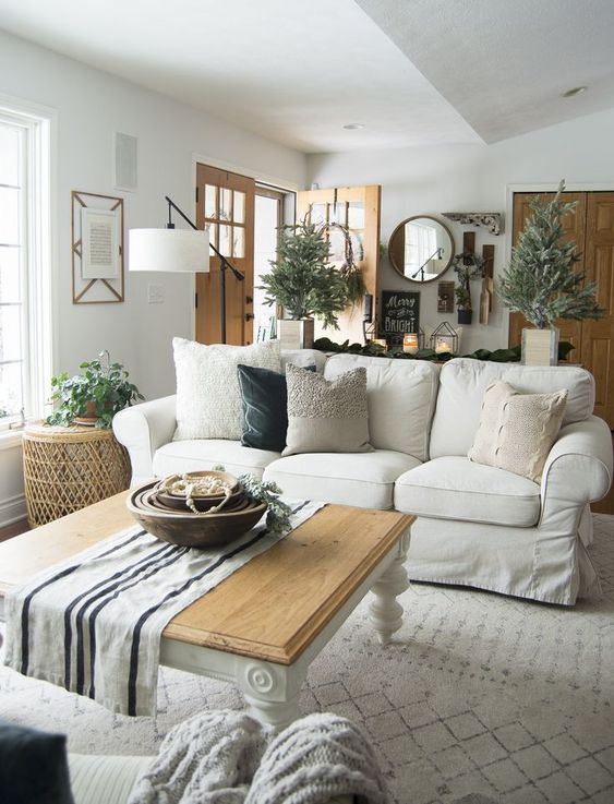 a white farmhouse living room with a white Ektorp, a low table, potted plants, a floor lamp and a round mirror