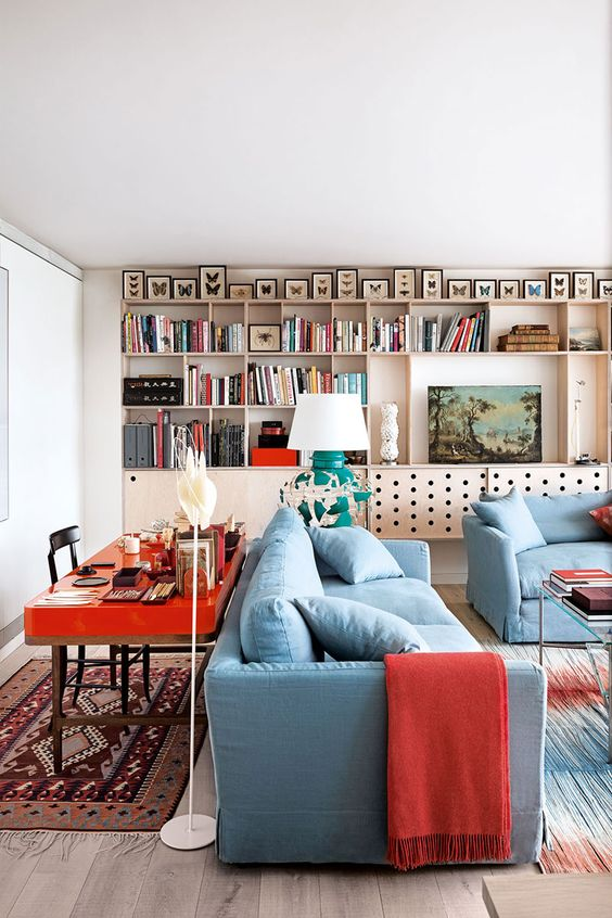 a bold living room with a plywood storage unit on the wall, butterflies, blue furniture, a hot red desk behind the sofa and bold red textiles