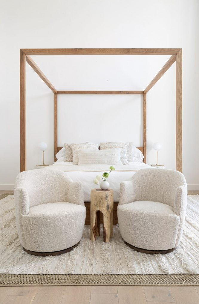 a chic and neutral bedroom with a wooden canopy bed, rounded creamy chairs, a tree stump side table and simple lamps