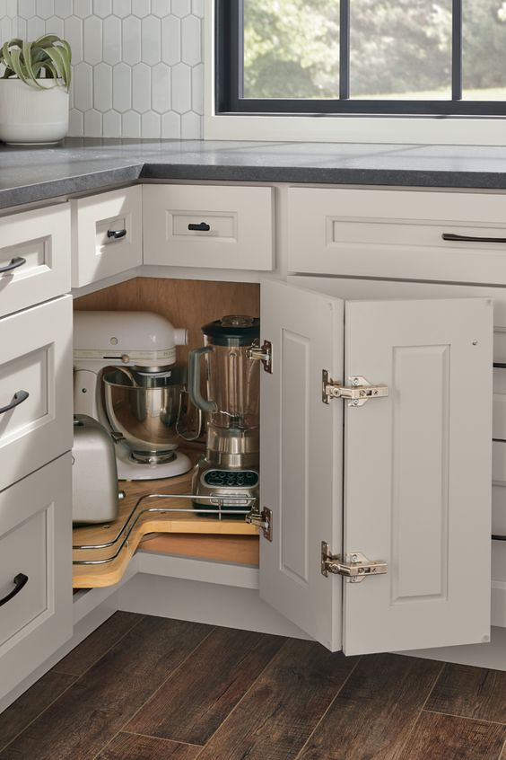 a lazy susan kitchen cabinet with a folding door and a large swivel compartment to hide kitchen appliances