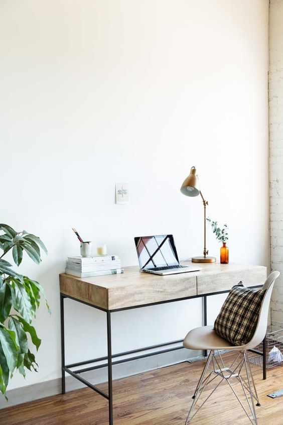 a modern working space with a plywood desk with drawers, a cool chair, a brass lamp and some greenery is sleek and serene