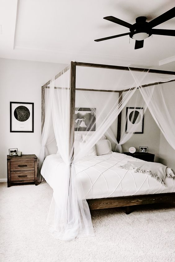 a monochromatic bedroom with dark stained furniture, a canopy bed with neutral bedding, cool artworks and a ceiling lamp