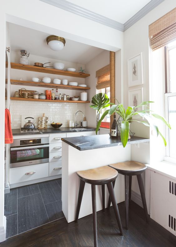 a small neutral kitchen with dark stone countertops, a small raised breakfast countertop and wooden stools   the countertop can double as acooking surface