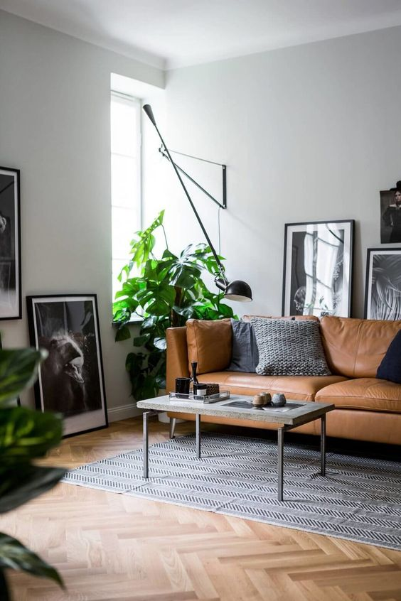a stylish Nordic living room with a tan leather Stockholm sofa, a low table and gorgeous black and white framed artworks