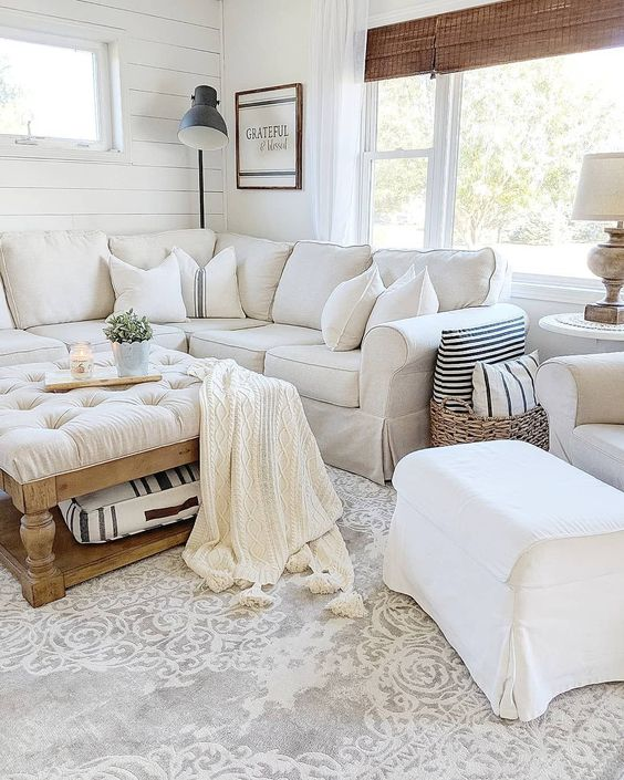 a white farmhouse living room with a sectional Ektorp, a white chair and footrest, a low tufted ottoman